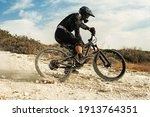 Professional bike rider fully equipped with protective gear during downhill ride on his bicycle