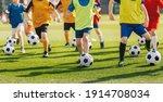 Small photo of Football soccer children training class. Kids practicing football on grass field. Group of school children running and kicking soccer balls on summer training camp