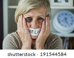 Small photo of Senior woman with black eye and tape on her mouth, victim of domestic violence