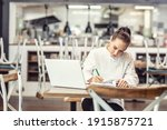 Small photo of Female restaurant chef sits at the table after hours doing her bookkeeping in front of an open laptop.
