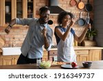 Small photo of Close up overjoyed African American couple singing into kitchenware, having fun, dancing, listening to music in kitchen, cooking salad, excited wife and husband holding whisk and ladle a microphone