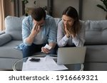 Small photo of Confused upset millennial married couple sit on couch read financial papers invoices troubled with too high expenses utility costs. Worried young spouses deal with debt bankruptcy of family business