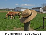Small photo of Amish straw hat laying on a fence post in a Lancaster Pennsylvania horse farm