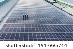 Small photo of Solar panels installed on a roof of a large industrial building or a warehouse. Industrial buildings in the background. Horizontal photo.