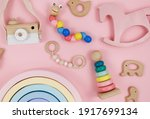 Small photo of Wooden baby toys on a pastel pink background. Horse, numbers, blocks, puzzle shapes, pyramid, rainbow, camera. Set of accessories for children. Early education, imagination, grasping training.