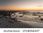 Small photo of A sunset scene overlooking the coast and harbor in Lambert's Bay, Western Cape, South Africa, West Coast area. The harbor buildings and harbor wall is visible.