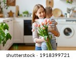 Small photo of Happy adult woman with tulips smiling with closed eyes and embracing boy in gratitude while celebrating holiday at home