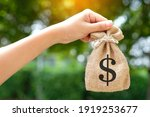 Small photo of Hand of a woman carrying a purse money .concept saving money and investment concept