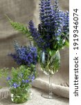 Small photo of Bouquets of forest blue flowers in glass vases on a burlap background. Ajuga reptans or bugle, bugleweed, blue bugle flowers with a green branch of field horsetail and Veronica persica flowers