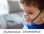 Small photo of Home treatment. The boy makes inhalation with a nebulizer inhaling medicines into his lungs. Self-treatment of the respiratory tract with inhalation. Little boy using nebulizer during inhaling therapy