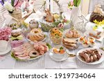 Small photo of traditional Easter dishes with white borscht, sausage, eggs, salad and cakes on festive table in Poland