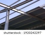 Small photo of Selective focused structure steel beams, metal pillar, crossbeams supported underneath metal sheets for roof construction. Structure steel, skeleton, girder, concept.