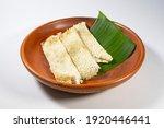 Small photo of rice cake from Bangladesh on clay dish. local name Binni chaler pathishapta pitha, goigga pitha, Puli, biroin chaler petha, binni rice pitha. Made by Forbidden Rice, coconut and sugar. Bengali food.