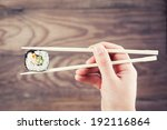 hand holding sushi roll using... | Shutterstock . vector #192116864