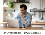 Small photo of Pensive young Caucasian man sit at table at home kitchen work online on laptop pondering thinking. Thoughtful millennial male look at computer screen browsing wireless internet on modern gadget.