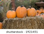 Three Pumpkins On A Bale Of Hay.
