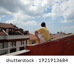 Young Man Sitting On The Roof...