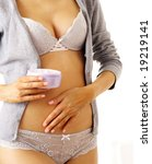 slim woman in panties applying body cream - stock photo