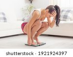 Young woman squats on a scale...