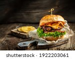 Small photo of Homemade burger with grilled beef meat, vegetables, sauce on rustic wooden background. fast food and junk food concept.