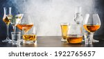 Small photo of Strong alcoholic drinks in glasses in assortment: vodka, cognac, tequila, brandy and whiskey, grappa, liqueur, vermouth, tincture, rum. Gray bar counter with copy space