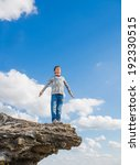 Small photo of teenager suicide acrophobia boy man stands on the precipice of a cliff height and fear of heights on a background of blue sky