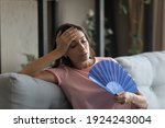 Small photo of Too hot. Exhausted indian female suffer from heat in modern apartment use hand fan feel lack of air conditioning. Unhappy young mixed race female complaining on high temperature at home hard to breath