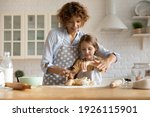 Small photo of Friendly young mother little daughter cook dessert bakery at modern kitchen knead dough with hands enjoy preparing cookies bread spend time together. Small girl learn to bake with help of caring mom