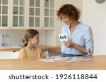 I like learning maths. Happy mother teach small child daughter mathematics using flash cards. Creative millennial female teacher help junior schoolgirl understand multiplication basics in form of game