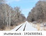 Small photo of Railroad tracks dwindle to thin lines in a cold winter landscape.
