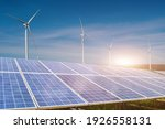 Small photo of solar panels with wind turbines against blue sky background. Photovoltaic, alternative electricity source. sustainable resources concept.
