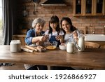 Small photo of Happy three generations of Hispanic women gather in kitchen cook delicious breakfast together. Smiling little girl with young mom and mature grandmother prepare pancakes or bake at home on weekend.