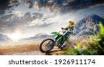 Small photo of Professional enduro bike rider on action. Turn on sand terrain.