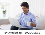 happy man sitting on couch... | Shutterstock . vector #192706619