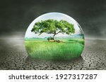 Close up of a drop water with green trees and farmland on dried soil. Global warming concept