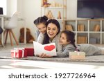 Small photo of Mother's Day. Twin sisters hug and greet their mother by giving her a handmade card and gifts. Excited happy mother lying on the floor with children and reading greetings. Concept of family and love.