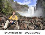 Happy man resting on rocks. Snoqualmie waterfall and rainbow behind him. Washington state. - stock photo