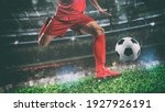 Small photo of Close up of a soccer scene at night match with player in a red uniform kicking the ball with power