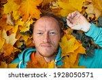 Man Lying On Fallen Leaves In...