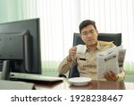 Small photo of Portrait of Asian Thai adult man wears A Thai government officer, a civil servant uniform, reading the newspaper and having a cup of coffee and relaxed time in the office.