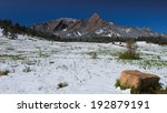 Boulder Flatirons Mountains with Light Spring Snow in Valley Foreground and Vivid Rocky Mountain Blue Sky - stock photo