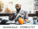 Small photo of Portrait of a baldheaded adult black dandy guy with a well-groomed beard, in a custom made elegant costume and eyeglasses sitting in a street cafe with a cup of delicious coffee and reading a magazine