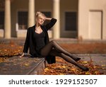 Beautiful blonde woman with perfect legs in pantyhose posing outdoor at the autumn street in the lights of the setting sun.