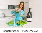 Small photo of Fresh homemade celery detox juice. Healthy young woman making freshly pressed celery juice in juicer machine at home. Healthy detox diet