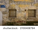 """Two wood old windows with iron bars. Translation : A greek street signboard  """"Ofonis Street"""" ."""