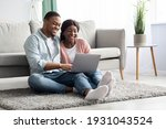 Small photo of Happy black lovers sitting on floor on carpet by couch with laptop, having fun together at home, copy space. Cheerful african american couple looking for new furniture online, websurfing