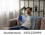 Small photo of Frustrated guy recline on sofa suffer from too hot temperature at home breath hard with dehydrated air cool down with hand fan. Tired young male complain on extra heat at living room feel bad sweaty