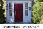 Small photo of A red door with white trim adorned by lanterns on either side, and green shrubs.