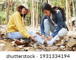 Small photo of A hiking-loving Asian woman is helping her best friend who was in an accidental flipping ankle in the forest. Travelers are providing first aid to an injured traveling companion.
