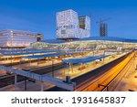 Utrecht, Netherlands cityscape over train station platforms at dawn.